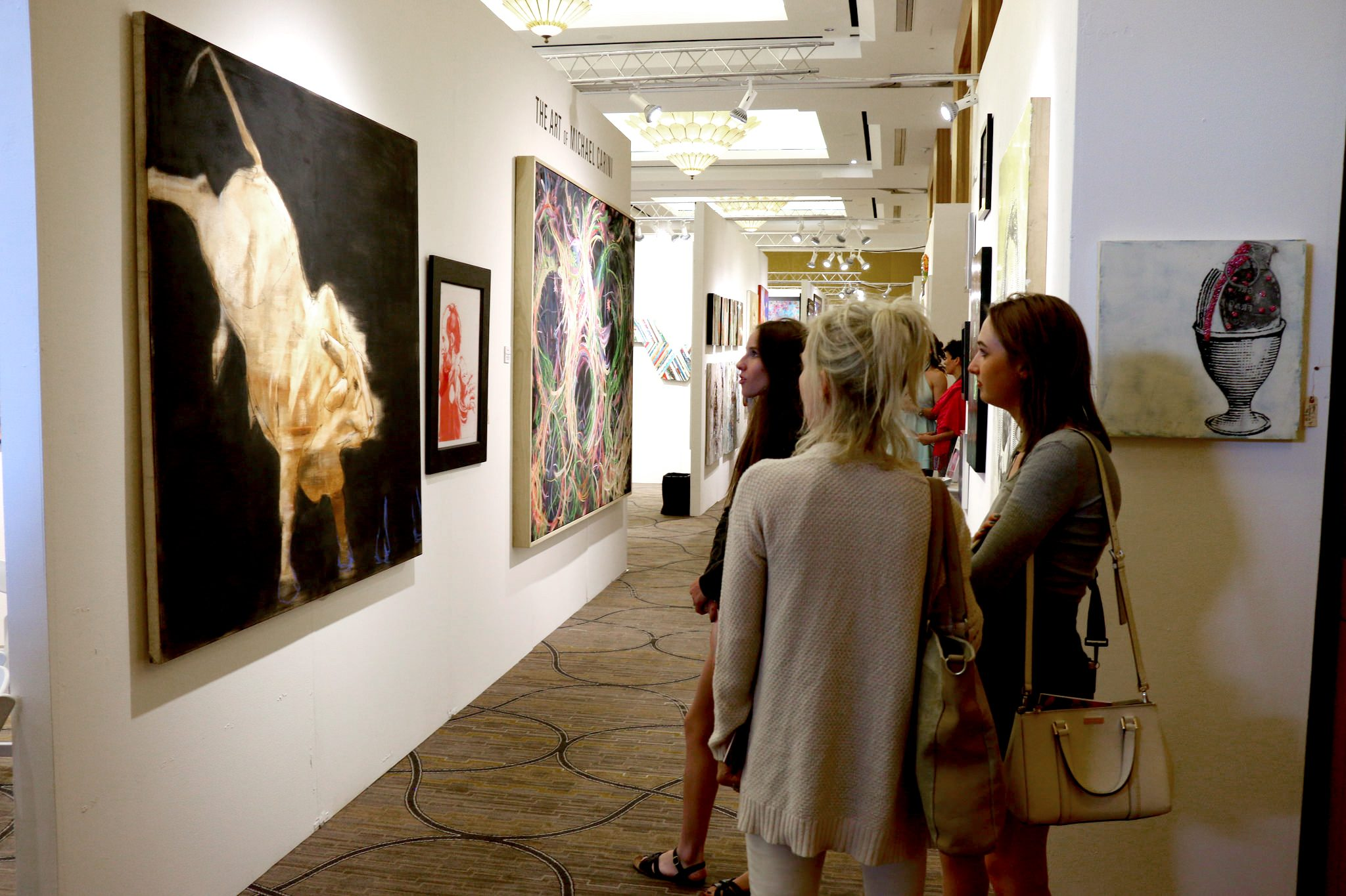 Attendees view paintings by Michael Dowling.