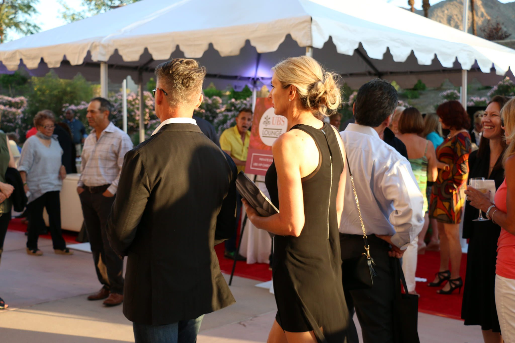 Attendees enjoy the warm evening weather as they make their way into the show.